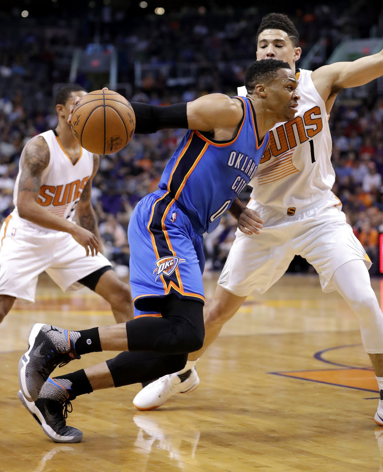 Photo - Oklahoma City Thunder guard Russell Westbrook (0) drives past Phoenix Suns guard Devin Booker (1) during the first half of an NBA basketball game, Friday, April 7, 2017, in Phoenix. (AP Photo/Matt York)