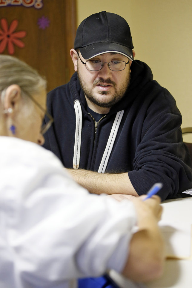 Photo -  Kyle Watts, of Moore, talks to registered nurse Tamie Spring about his health history during the Hope Medical Clinic at the Slaughterville Baptist Church. [PHOTO BY NATE BILLINGS, THE OKLAHOMAN]