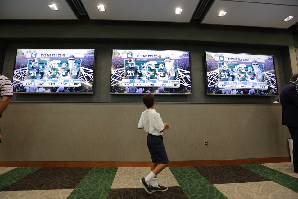 Photo - In this Monday, Aug. 25, 2014, photo, John Abood, of East Lansing, watches large screen televisions during a tour of the new North End Zone Complex renovations at Spartan Stadium on the Michigan State Campus in East Lansing, Mich. (AP Photo/Detroit Free Press, Ryan Garza)  DETROIT NEWS OUT, TV OUT, INTERNET OUT, MAGS OUT, NO SALES, MANDATORY CREDIT DETROIT FREE PRESS