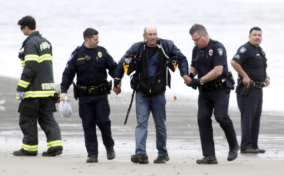 Photo - One of three people rescued from a stolen 82-foot long sailboat is arrested by police in Pacifica, Calif., where the boat ran aground Monday March 4, 2013. Three people were arrested Monday after they stocked a stolen yacht with pizza and beer, and then ran the vessel aground on a Northern California beach, authorities said. The boat was stolen from Sausalito, Calif. (AP Photo/Bay Area News Group, Karl Mondon)