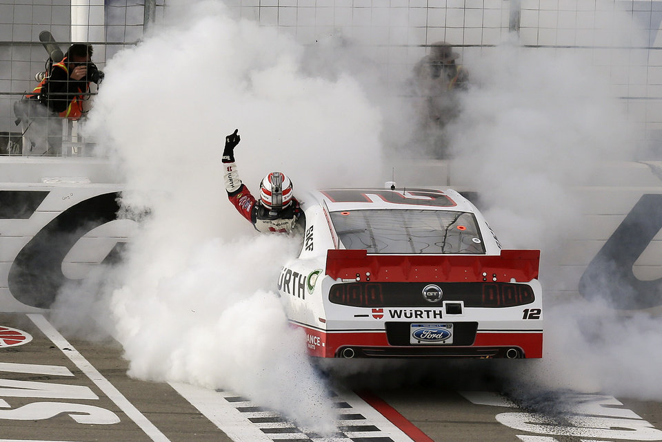 Sam Hornish Jr. waves to fans as he hangs out his window while doing a burnout after winning the NASCAR Nationwide Series auto race, Saturday, March 9, 2013 in Las Vegas. (AP Photo/Julie Jacobson)