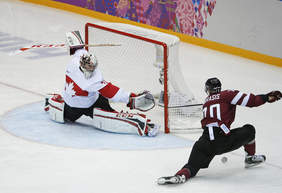 Photo - Canada goaltender Carey Price blocks a shot by Latvia forward Miks Indrasis during the second period of a men's quarterfinal ice hockey game at the 2014 Winter Olympics, Wednesday, Feb. 19, 2014, in Sochi, Russia. (AP Photo/Mark Humphrey)