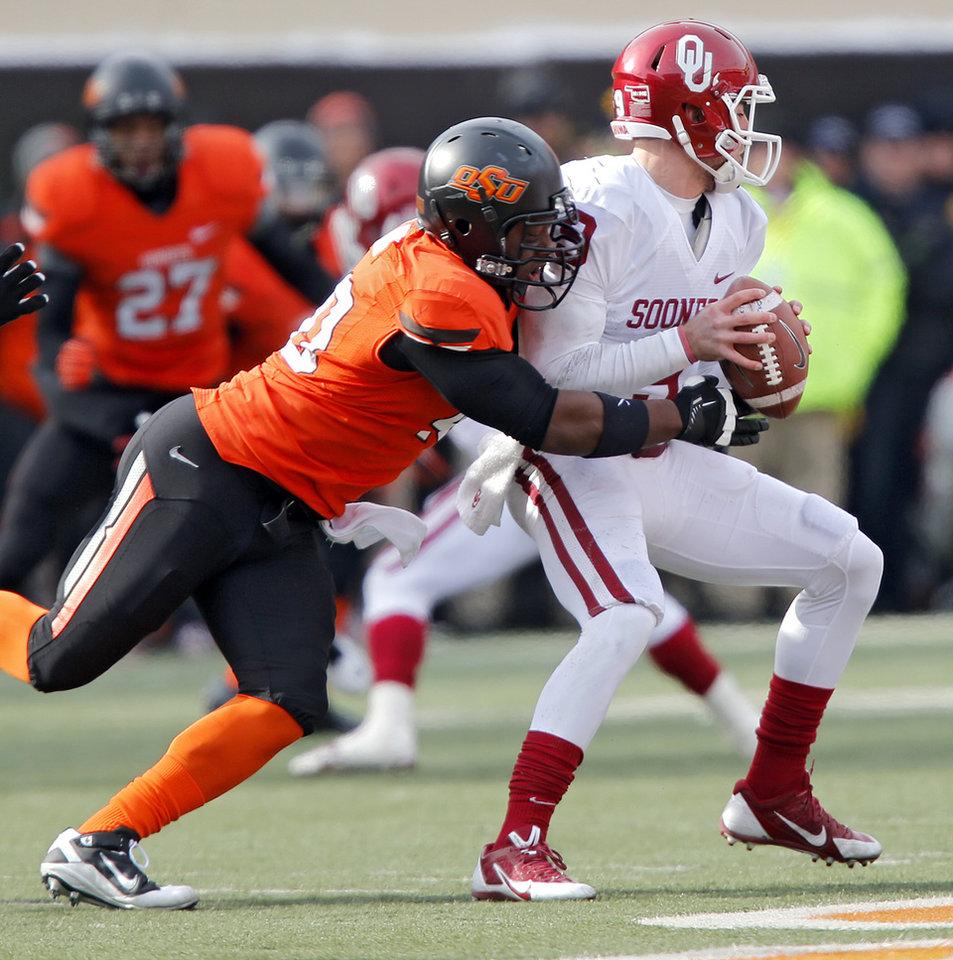 Oklahoma State's Tyler Johnson (40) sacks Oklahoma's Trevor Knight (9) during the Bedlam college football game between the Oklahoma State University Cowboys (OSU) and the University of Oklahoma Sooners (OU) at Boone Pickens Stadium in Stillwater, Okla., Saturday, Dec. 7, 2013. Photo by Chris Landsberger, The Oklahoman