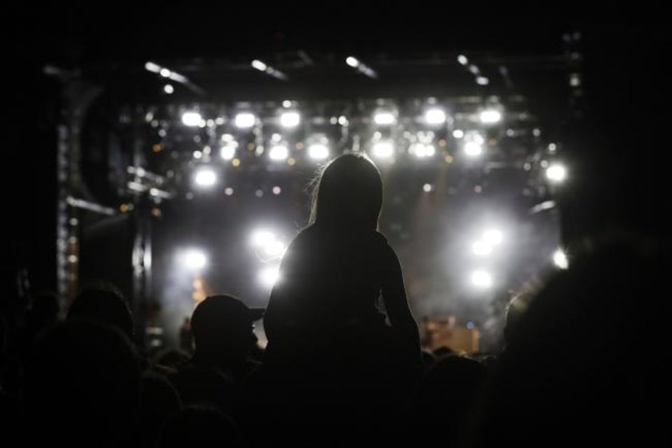 Photo -  A child sits on an adult's shoulders while watching Kings of Leon perform Friday. [Nate Billings/The Oklahoman]