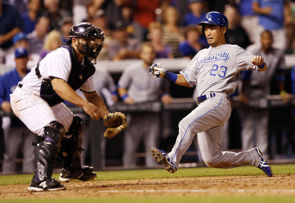 Photo - Kansas City Royals' Norichika Aoki starts to slide safe into home against Colorado Rockies catcher Michael McKenry during the seventh inning of a baseball game Tuesday, Aug. 19, 2014, in Denver. (AP Photo/Jack Dempsey)