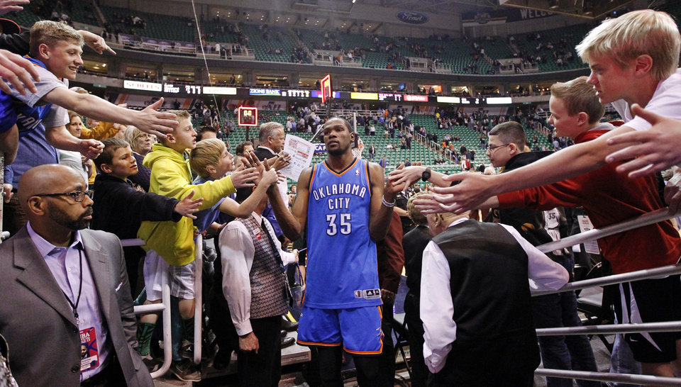 Fans reach for Oklahoma City Thunder\'s Kevin Durant (35) at the end of an NBA basketball game against the Utah Jazz, Tuesday, April 9, 2013, in Salt Lake City. The Thunder won 90-80. (AP Photo/Rick Bowmer) ORG XMIT: UTRB113