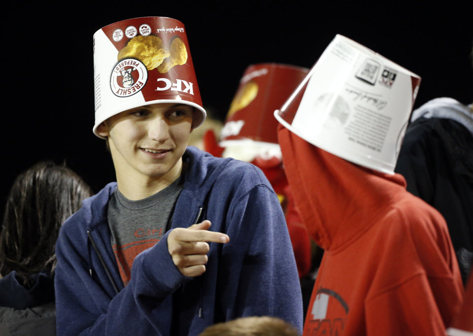"Photo - Carl Albert fans Karsen Klies and Rock Wallace wear buckets signifying ""fried bird"" as the Carl Albert Titans play the Del City Eagles on Friday, Nov. 15, 2013  in Midwest City, Okla. Photo by Steve Sisney, The Oklahoman"