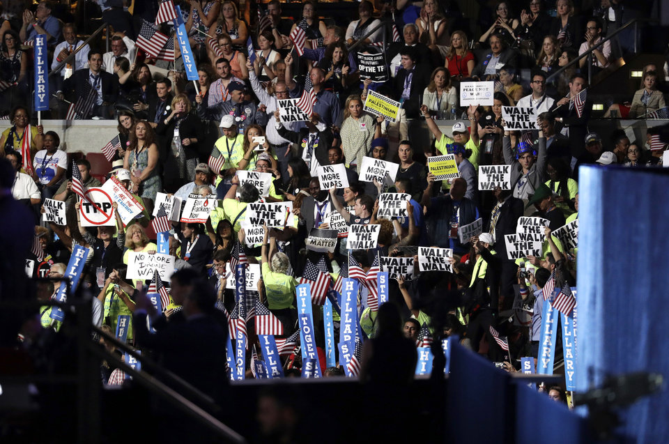 Photo - People hold up signs in protest as Democratic presidential nominee Hillary Clinton speaks during the final day of the Democratic National Convention, Thursday, July 28, 2016, in Philadelphia. (AP Photo/John Locher)