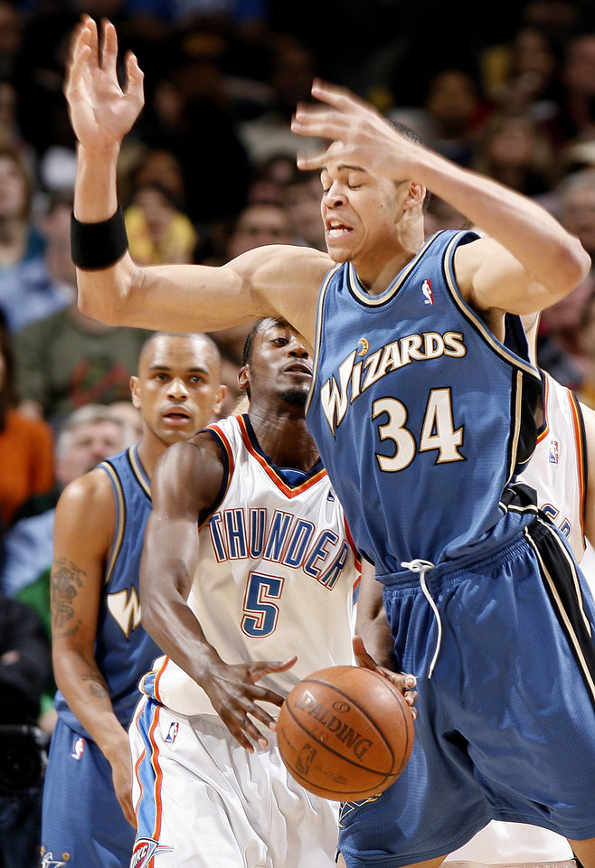 Oklahoma City's Kyle Weaver grabs the ball under Washington's JaVale McGee during the NBA basketball game between the Oklahoma City Thunder and the Washington Wizards at the Ford Center in Oklahoma City, Wed., March 4, 2009. PHOTO BY BRYAN TERRY, THE OKLAHOMAN
