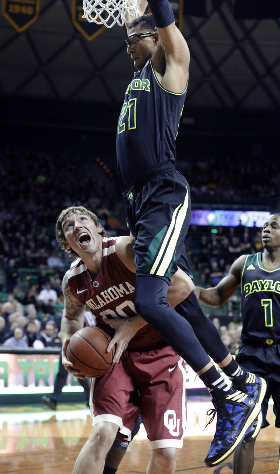 Photo - Oklahoma forward Ryan Spangler (00) is hit under the basket by defending Baylor center Isaiah Austin (21) during the first half of an NCAA college basketball game Saturday, Jan. 18, 2014, in Waco, Texas. (AP Photo/LM Otero)