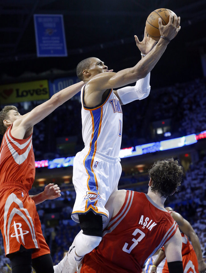 Oklahoma City Thunder guard Russell Westbrook (0) is fouled by Houston Rockets center Omer Asik as he shoots in the fourth quarter of Game 2 in their first-round NBA basketball playoff series in Oklahoma City, Wednesday, April 24, 2013. Oklahoma City won 105-102. (AP Photo/Sue Ogrocki)