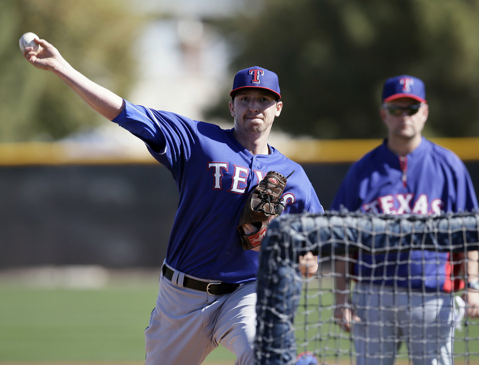 Photo - Texas Rangers' Tanner Scheppers throws during batting practice for spring training baseball practice, Monday, Feb. 17, 2014, in Surprise, Ariz. (AP Photo/Tony Gutierrez)