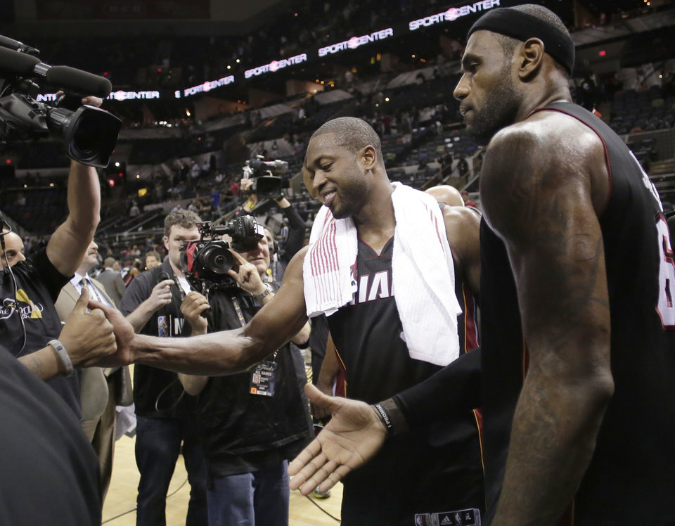 Photo - Miami Heat's Dwyane Wade, left, and LeBron James leave the floor after beating San Antonio Spurs at Game 4 of the NBA Finals basketball series, Thursday, June 13, 2013, in San Antonio. The Heat won 109-93. (AP Photo/Eric Gay)
