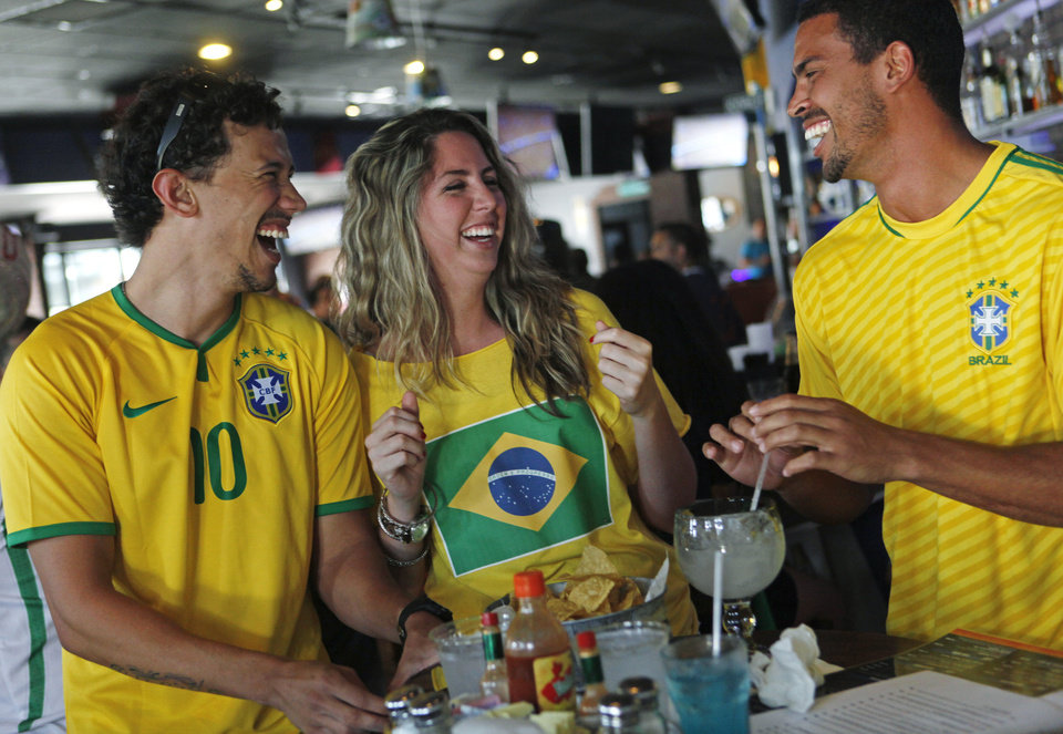 Photo -  Brazilian fans Ricardo Lima, Melissa Gomes and Peterson Neri — all from Brazil — laugh Tuesday during a World Cup watch party for the Brazil versus Mexico game at Medio Tiempo Sports Cantina and Grill. Photo by K.T. King, The Oklahoman   KT King