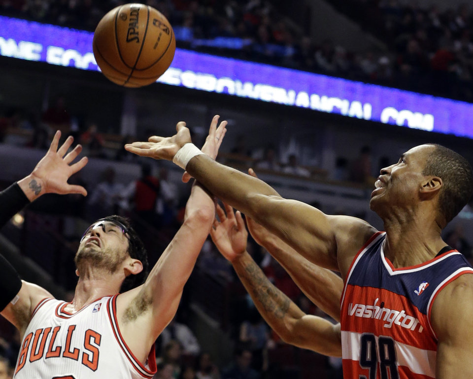 Photo - FILE - In this April 17, 2013 file photo, Washington Wizards center Jason Collins, right, battles for a rebound against Chicago Bulls guard Kirk Hinrich during the first half of an NBA basketball game in Chicago. Jason Collins has become the first male professional athlete in the major four American sports leagues to come out as gay. Collins wrote a first-person account posted Monday on Sports Illustrated's website. The 34-year-old Collins has played for six NBA teams in 12 seasons. He finished this past season with the Washington Wizards and is now a free agent. He says he wants to continue playing.  (AP Photo/Nam Y. Huh, File)