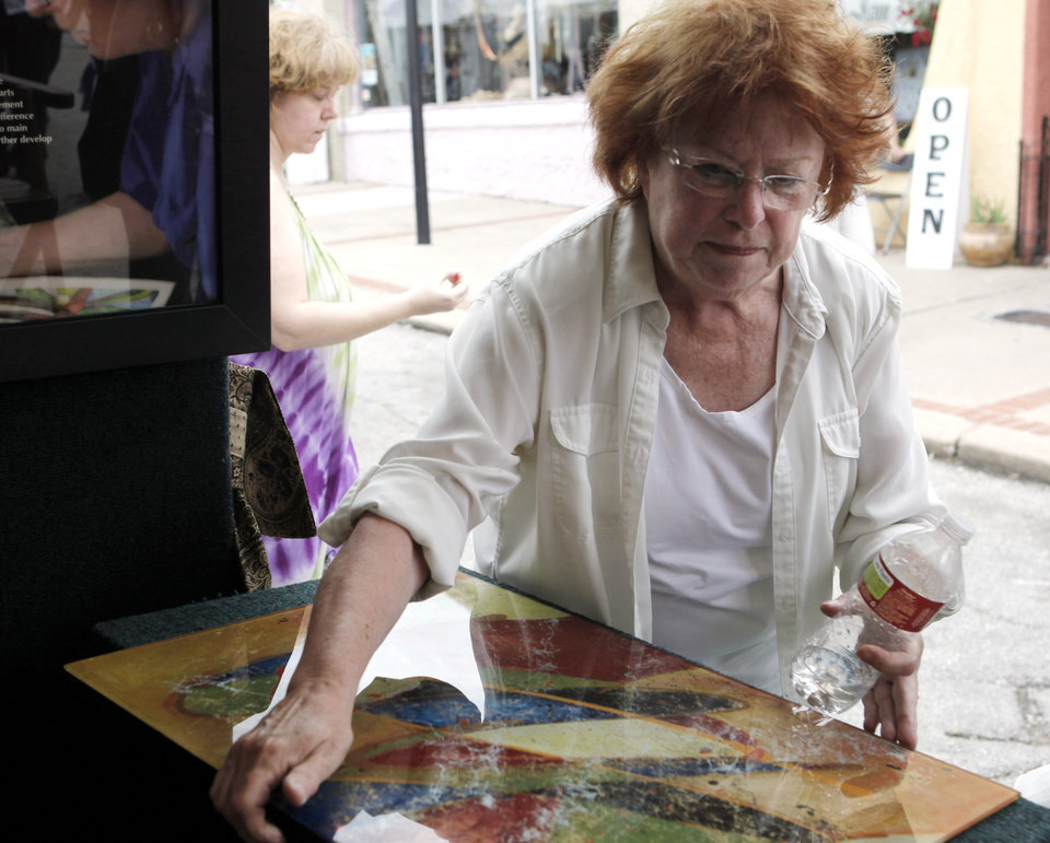 Photo -  Jan Brieschke, of Bartlesville, shows a vividly colored oil painting on glass at last year's Paseo Arts Festival. Photo by K.T. King, The Oklahoman Archives   KT King -