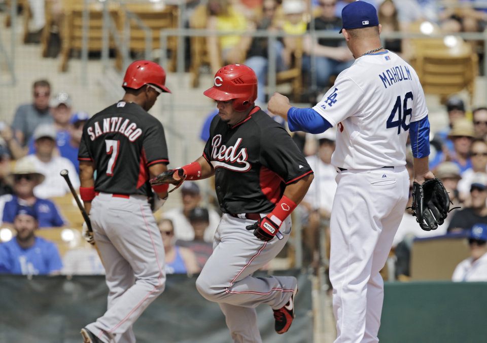 Photo - onCincinnati Reds' Brayan Pena, center, comes home to score on a wild pitch by Los Angeles Dodgers starting pitcher Paul Maholm (46) in the second inning of a spring exhibition baseball game on Thursday, March 13, 2014, in Glendale, Ariz. (AP Photo/Mark Duncan)