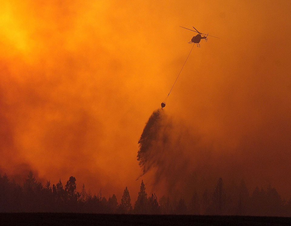 Photo - As the sun sets behind the plume of smoke, a helicopter makes a water drop on a fire Monday, Aug. 13, 2007, near Orofino, Idaho. Across Idaho, hundreds of homes were threatened by wildfires that have blackened more than 500,000 acres or 781 square miles, the National Interagency Fire Center said. Idaho experienced one of its worst wildfire seasons, with 1,151 wildfires tallied and a nation-leading 2,600 square miles burned, the most in the state since 2007, according to the National Interagency Fire Center. (AP Photo/ Lewiston Tribune, Steve Hanks)