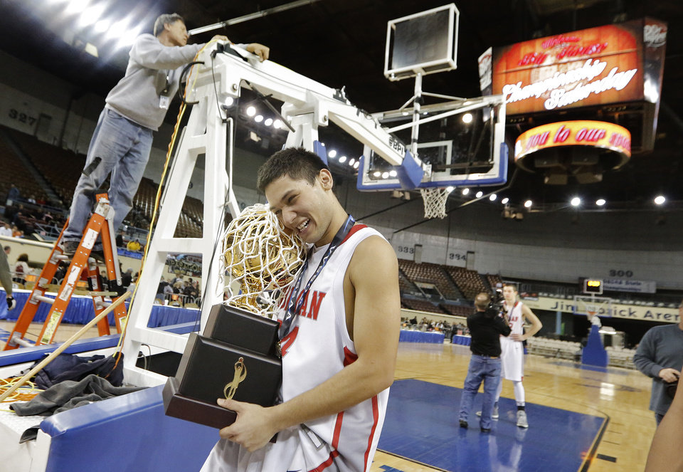 Photo - Forgan's Luis Ordonez (24) hugs the gold ball trophy as he leaves the court after the Bulldogs won the Class B boys high school basketball state championship game between Forgan and Lookeba-Sickles at the State Fair Arena in Oklahoma City, Okla., on Saturday, March 8, 2014.  Photo by Chris Landsberger, The Oklahoman
