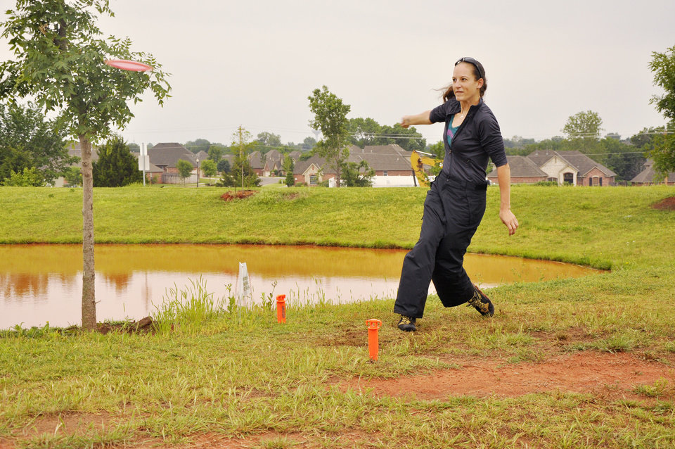 Kate Schwartz participates in the fourth annual Tye Cunningham disc golf tournament in Edmond. The tournament is named after the late Tye Cunningham, who led the way to get a disc golf course built in Edmond. PHOTO BY M. TIM BLAKE, FOR THE OKLAHOMAN. M. Tim Blake - FOR THE OKLAHOMAN