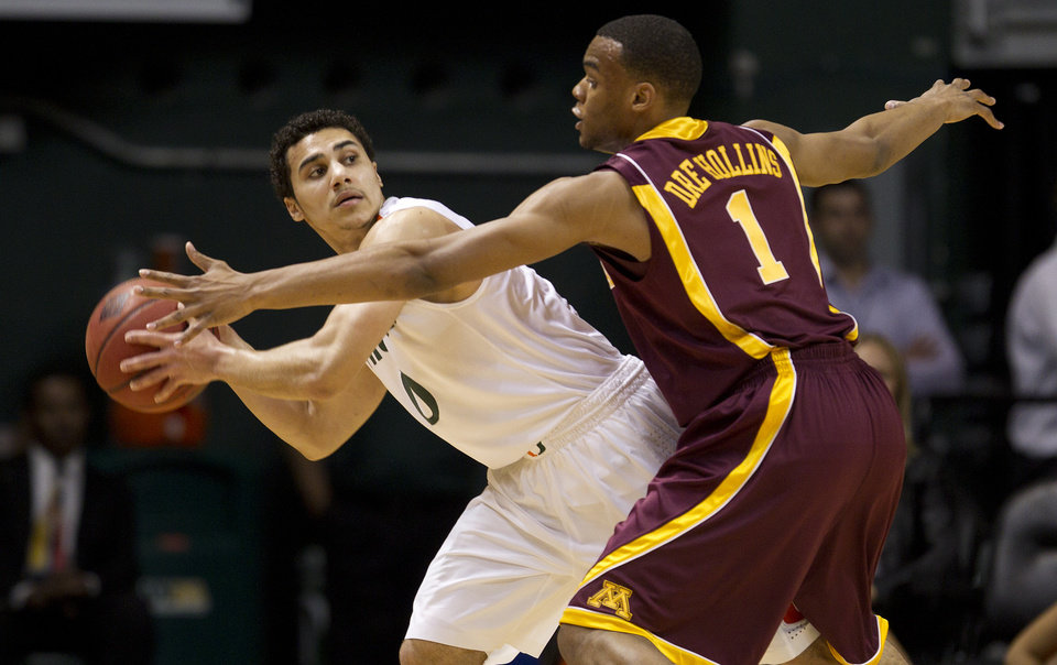 Photo -   Minnesota' Andre Hollins (1) forces Miami's Shane Larkin to pass the ball off during the first half of the second round of the NIT tournament NCAA college basketball game in Coral Gables, Fla., Monday, March 19, 2012. (AP Photo/J Pat Carter)
