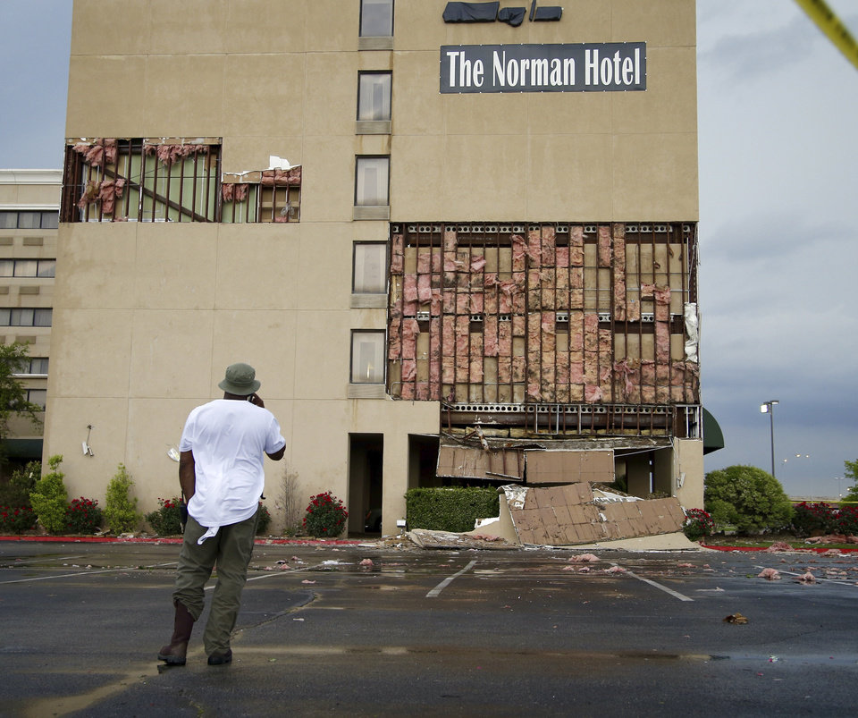 Photo - A man looks at damage to The Norman Hotel at Robinson and Interstate 35 in Norman, Okla., after a storm producing tornadoes passed through the area, Wednesday, May 6, 2015. Photo by Bryan Terry, The Oklahoman