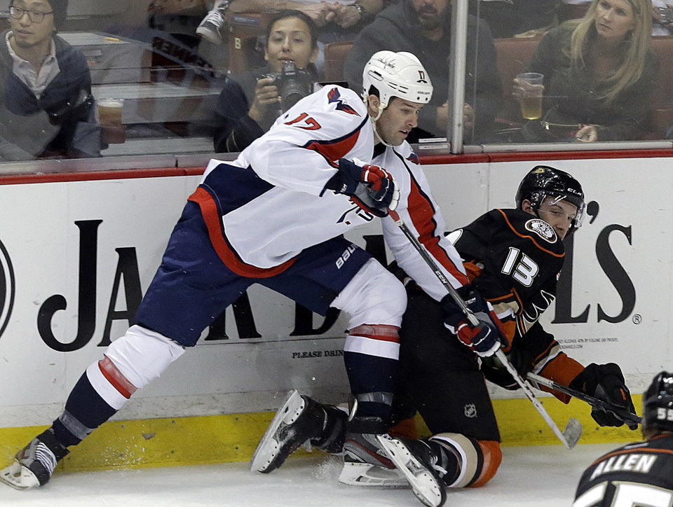 Photo - Washington Capitals right winger Dustin Penner (17) tangles with Anaheim Ducks center Nick Bonino (13) during the second period of an NHL hockey game Tuesday, March 18, 2014, in Anaheim, Calif. (AP Photo/Reed Saxon)