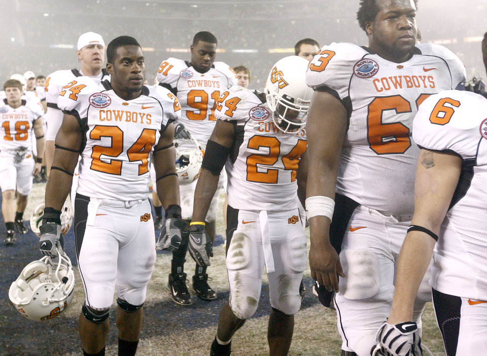 Photo - Deron Fontenot, left, Kendall Hunter, and David Washington of OSU walk off the field after their loss during the Holiday Bowl college football between Oklahoma State and Oregon at Qualcomm Stadium in San Diego, Tuesday, Dec. 30, 2008.  PHOTO BY BRYAN TERRY, THE OKLAHOMAN.