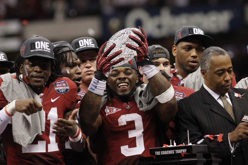FILE - In this Jan. 9, 2012, file photo, Alabama running back Trent Richardson holds up the championship trophy after winning the BCS National Championship NCAA college football game against LSU, in New Orleans. College football may finally get a playoff system of sorts, if the rumblings out of the Big Ten this week are any indication of the current thought process. The conference that helped spike the idea of teams actually earning their spots in the national title game when it was proposed four years ago, seems to be warming up to it now. (AP Photo/Dave Martin, File) ORG XMIT: NY167