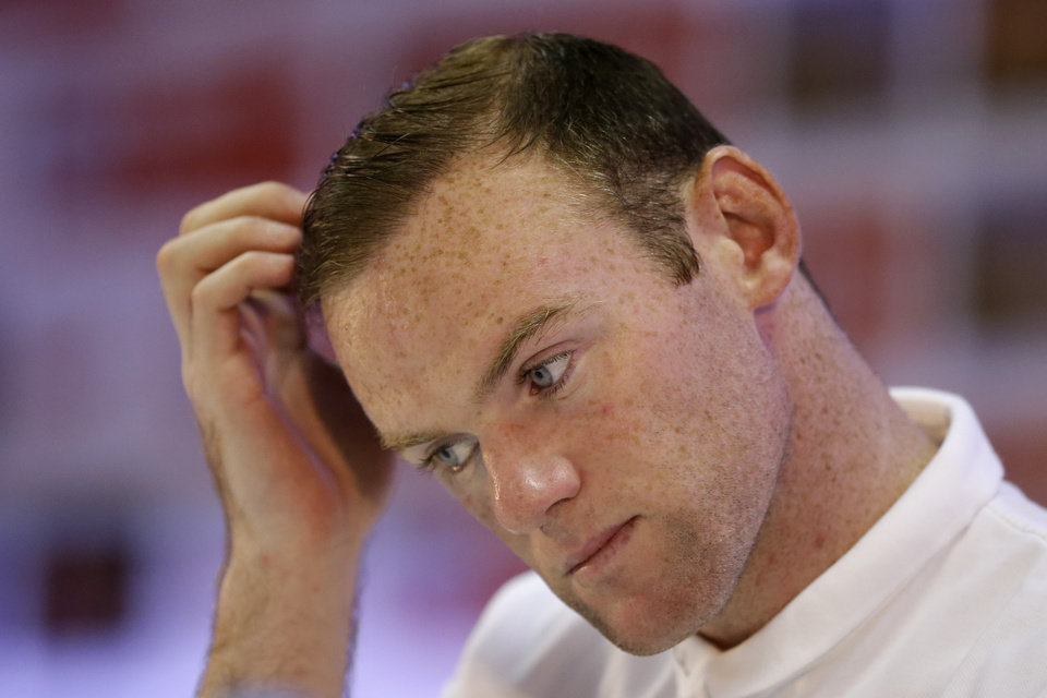 Photo - England national soccer team player Wayne Rooney holds his hand to his head during a press conference after a squad training session for the 2014 soccer World Cup at the Urca military base in Rio de Janeiro, Brazil, Saturday, June 21, 2014.  Costa Rica's surprise 1-0 win over Italy on Friday meant that England made its most humiliating exit from a World Cup since 1958, following consecutive defeats by the Italians and then Uruguay in Group D.  England play Costa Rica in their final Group D match on Tuesday.  (AP Photo/Matt Dunham)
