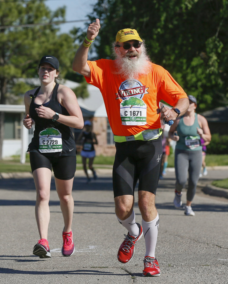 Photo - Charles Redditt gives thumbs up to police officers working the course to direct runners out of the neighborhood at Somerset and NW Grand Blvd. during the Oklahoma City Memorial Marathon in Oklahoma City, Sunday, April 28, 2019. [Nate Billings/The Oklahoman]