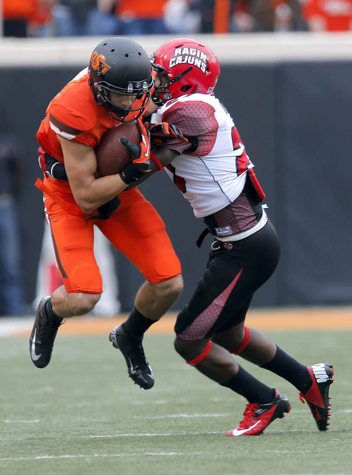 Oklahoma State\'s Charlie Moore (17) makes a catch as Louisiana-Lafayette\'s T.J. Worthy (27) defends during a college football game between Oklahoma State University (OSU) and the University of Louisiana-Lafayette (ULL) at Boone Pickens Stadium in Stillwater, Okla., Saturday, Sept. 15, 2012. Photo by Sarah Phipps, The Oklahoman