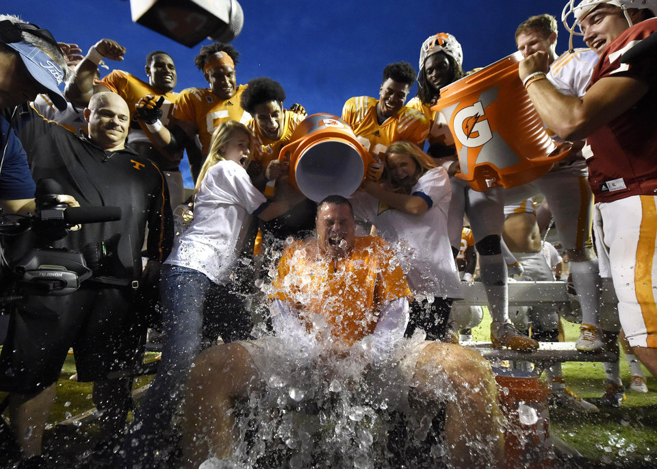 Photo - Tennessee coach Butch Jones, center, gets a cooler of ice dumped on him while participating in the Ice Bucket Challenge at the conclusion of the Tennessee football team's open practice at Neyland Stadium in Knoxville, Tenn., on Saturday, Aug. 16, 2014. (AP Photo/Knoxville News Sentinel, Adam Lau)