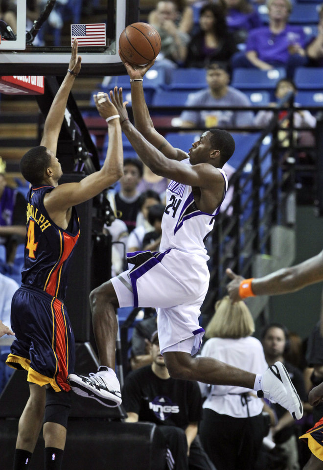 Photo - Sacramento Kings forward Desmond Mason, right, drives to the basket against Golden State Warriors forward Anthony Randolph during the second quarter of an NBA preseason game in Sacramento, Calif., Saturday, Oct. 17, 2009.  (AP Photo/Rich Pedroncelli) ORG XMIT: SCA103
