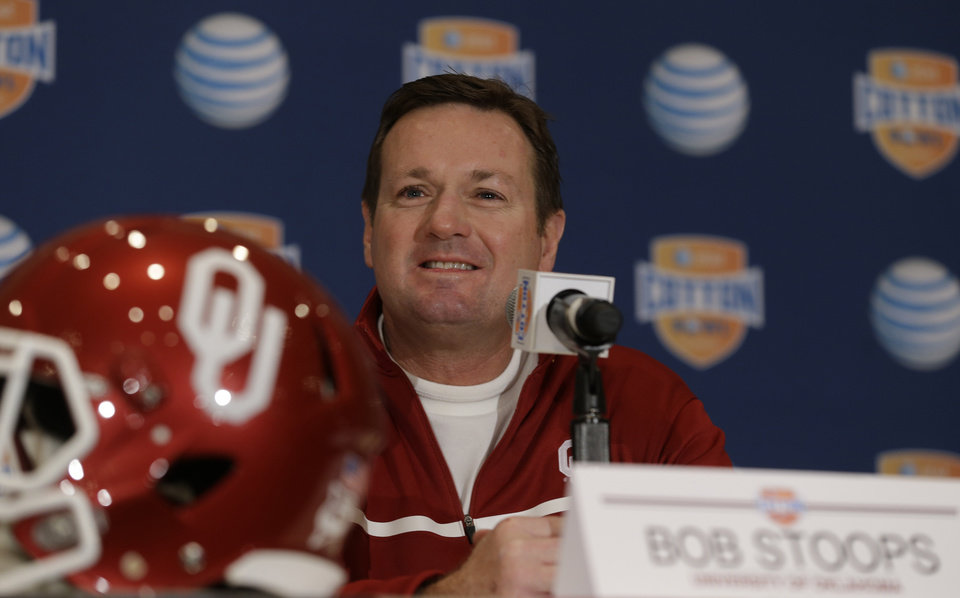 Photo - Oklahoma head coach Bob Stoops smiles as he answers a question during a news conference leading up to the Cotton Bowl NCAA college football game Wednesday, Jan. 2, 2013, in Irving, Texas. Before Texas A&M head coach Kevin Sumlin became a succesful head coach, he was on Stoops' staff at Oklahoma. Before that, they were both assistant coaches recruiting the same area. Now Sumlin takes his Texas A&M team against Stoops' Sooners in a Jan. 4th Cotton Bowl matchup of former Big 12 rivals that are both 10-2. (AP Photo/LM Otero) ORG XMIT: TXMO105