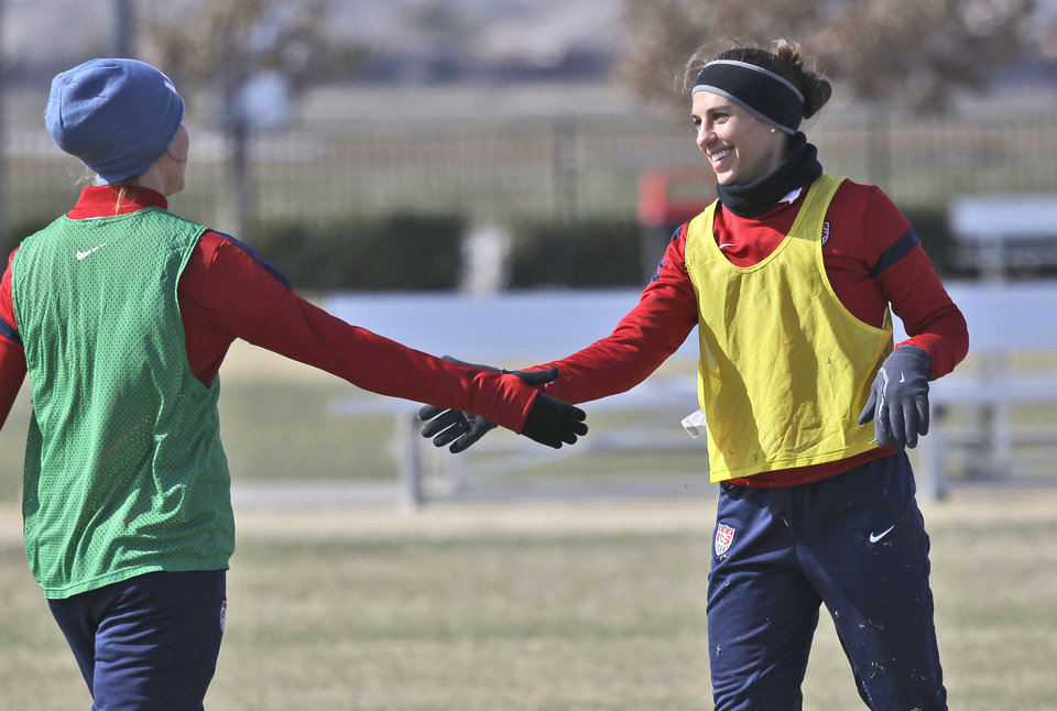 Photo - In this photo made Tuesday, Jan. 28, 2014, U.S. women's soccer team players Carli Lloyd, right, reaches to shake hands with a teammate during practice in Frisco, Texas. The U.S. women's soccer team opens its season against Canada in Texas on Friday, Jan. 31, their second meeting since the 2012 Olympic match. (AP Photo)