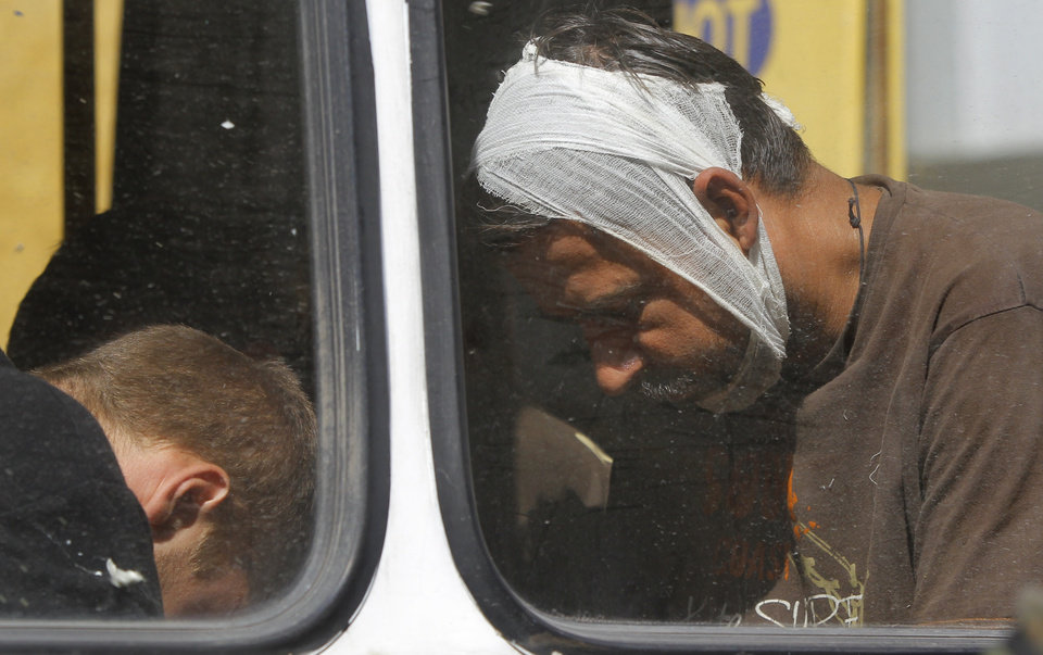 Photo - Captured Ukrainian army prisoners sit in a bus after they were escorted by Pro-Russian rebels in Donetsk, eastern Ukraine, Sunday, Aug. 24, 2014. Ukraine has retaken control of much of its eastern territory bordering Russia in the last few weeks, but fierce fighting for the rebel-held cities of Donetsk and Luhansk persists. (AP Photo/Sergei Grits)