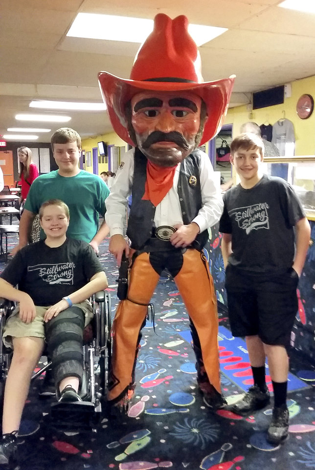 Photo - Alleyn Campbell and his brothers pose for a photo with Pistol Pete. Alleyn was injured during the crash at Oklahoma State UniversityÕs homecoming parade. [Photo provided]