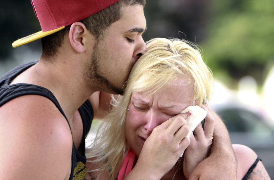 Photo - Two people comfort each other as they await word about the safety of students after a shooting at Reynolds High School, Tuesday, June 10, 2014, in Troutdale, Ore. A gunman killed a student at the high school east of Portland Tuesday and the shooter is also dead, police said. (AP Photo/The Oregonian, Faith Cathcart)