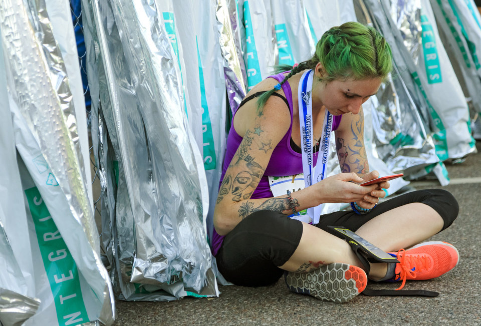 Photo - Loren Hannah uses her cell phone as she recovers after taking part in the 5K race during the Oklahoma City Marathon in Oklahoma City, Okla. on Sunday, April 29, 2018.  . Photo by Chris Landsberger, The Oklahoman