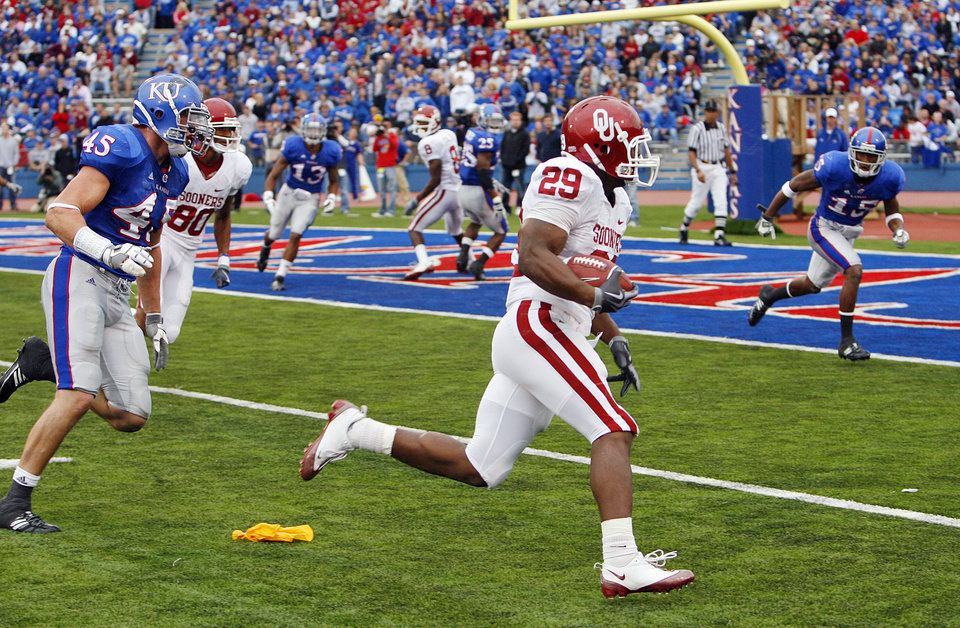 Photo - Oklahoma's Chris Brown rounds the outside past Kansas' Justin Springer (45) to score a touchdown during the second half of the college football game between the University of Oklahoma Sooners (OU) and the University of Kansas Jayhawks (KU) on Saturday, Oct. 24, 2009, in Lawrence, Kan. Oklahoma won the game 35-13. Photo by Chris Landsberger, The Oklahoman