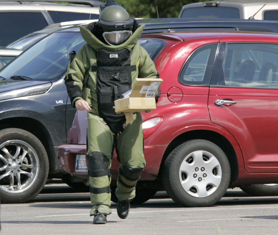 Photo - A  bomb squad technician carries a suspicious package in May 2010 at the state Capitol.  Photo by Steve Gooch, The Oklahoman Archives