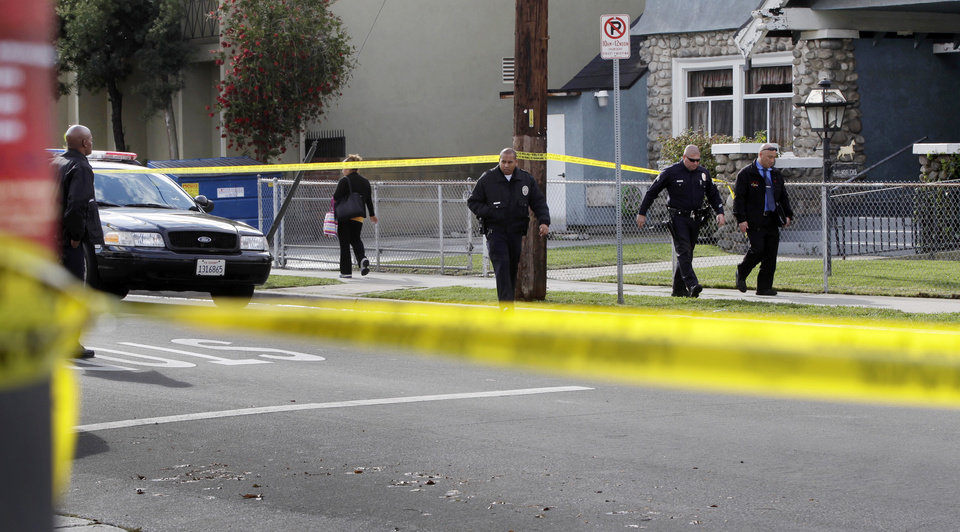 Photo -   Los Angeles Police Department officers and investigators work at the scene of a shooting of two USC students in Los Angeles on Wednesday, April 11, 2012. Police said a gunman opened fire on a BMW near the University of Southern California campus on Wednesday, killing two international students from China in what may have been a bungled carjacking attempt. (AP Photo Damian Dovarganes)