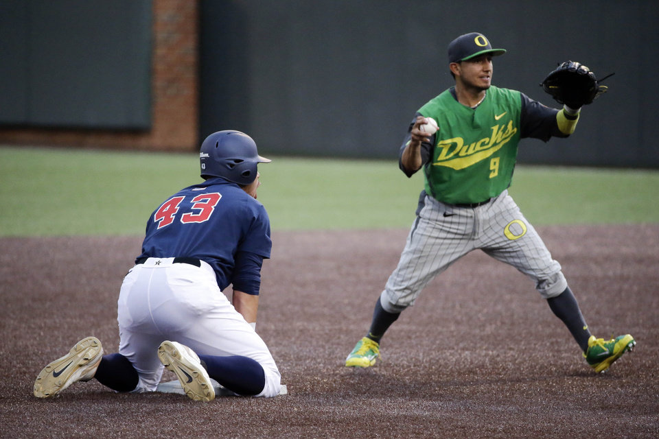 Photo - Oregon shortstop Kevin Minjares (9) shows the ball to the umpire after beating Vanderbilt's Zander Wiel (43) back to second base to complete a double play during the second inning of an NCAA college baseball regional tournament game Sunday, June 1, 2014, in Nashville, Tenn. (AP Photo/Mark Humphrey)