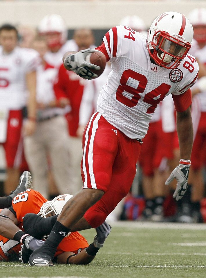 Photo - Nebraska's Brandon Kinnie slips past OSU's Devin Hedgepeth on a touchdown run during the college football game between the Oklahoma State Cowboys (OSU) and the Nebraska Huskers (NU) at Boone Pickens Stadium in Stillwater, Okla., Saturday, Oct. 23, 2010. Photo by Sarah Phipps, The Oklahoman