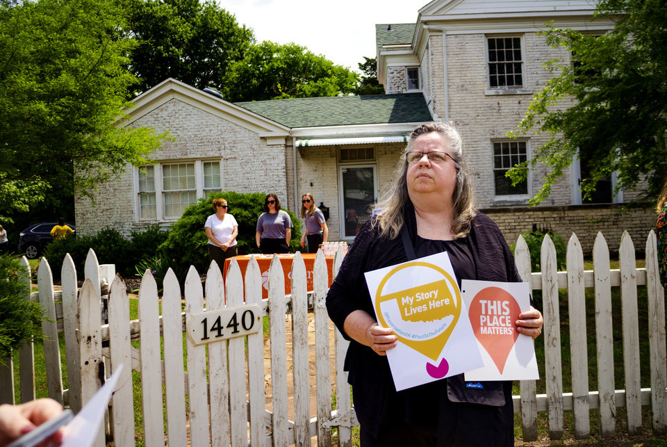 Photo -  Catherine Montgomery carries signs during a Preservation Oklahoma rally May 6 for the historic Brockway Community Center at 1440 N. Everest Ave. in Oklahoma City. The site's current owners have a permit to demolish the center, but said they will listen to alternatives from the city's Urban Renewal Authority. [Chris Landsberger/The Oklahoman]