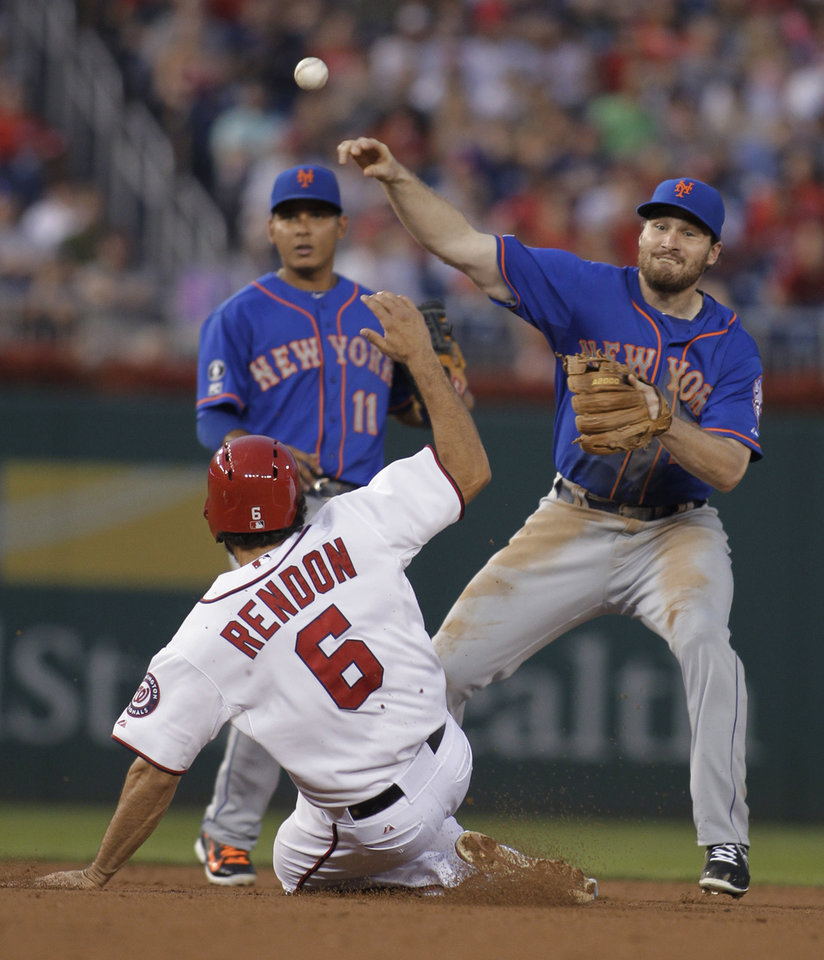 Photo - New York Mets second baseman Daniel Murphy throws to first on a double play, over Washington Nationals' Anthony Rendon, as shortstop Ruben Tejada watches during the third inning of a baseball game, Tuesday, Aug. 5, 2014, in Washington. Jayson Werth was out at first. (AP Photo/Luis M. Alvarez)