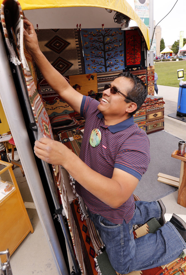 Photo -  Mel Mendez hangs rugs at his booth during the Festival of the Arts in Bicentennial Park. [PHOTO BY STEVE SISNEY, THE OKLAHOMAN]