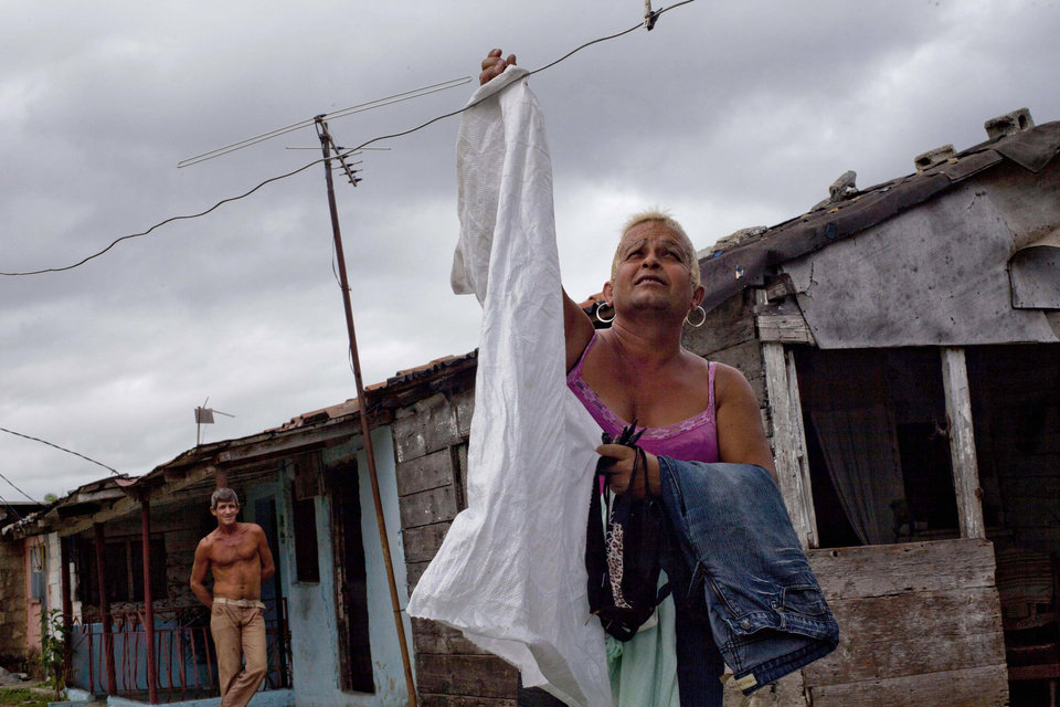 """Adela Hernandez, 48, gathers the laundry from a clothesline outside her home in the village of Caibarien, Cuba, Friday, Nov. 16, 2012. Hernandez, a biologically male Cuban who has lived as a female since childhood, served two years in prison in the 1980s for """"dangerousness"""" after her own family denounced her sexuality. This month she made history by becoming the first known transgender person to hold public office in Cuba, winning election as a delegate to the municipal government of Caibarien in the central province of Villa Clara. (AP Photo/Ramon Espinosa)"""