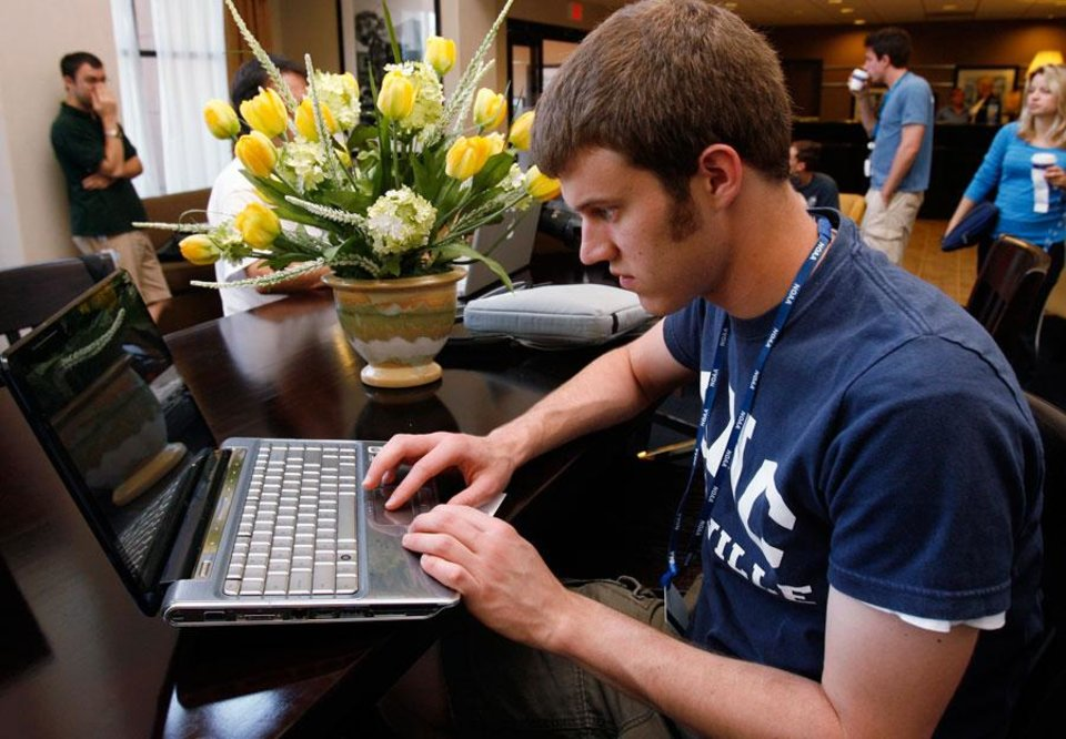 Photo -  Jacob Carley, Purdue, uses his computer in luxuary in the lobby of the hotel as VORTEX2 prepares to leave the panhandle of Texas back to Oklahoma on Wednesday, May 13, 2009.  Photo by Steve Sisney, The Oklahoman